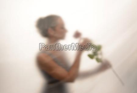 giovane donna con rosa dietro lamina