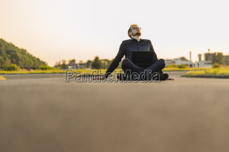 businessman sitting on rural road with
