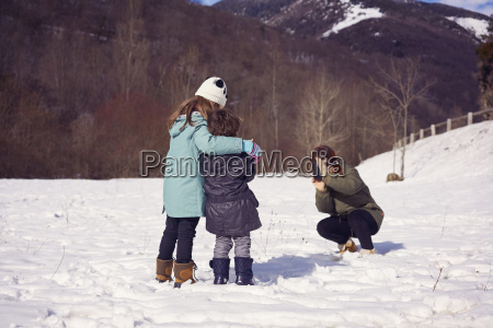 mother taking picture of two children