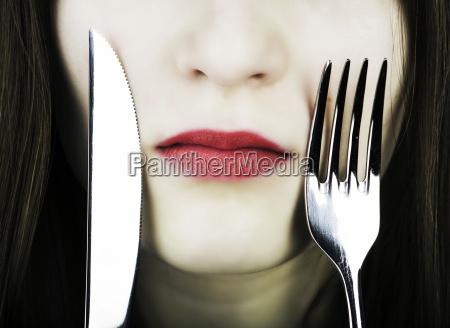 adolescente con coltello e forchetta sul