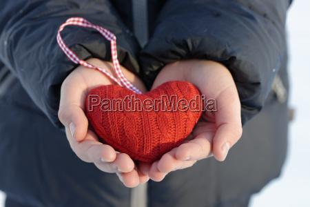 mani che tengono cuore tricottato rosso