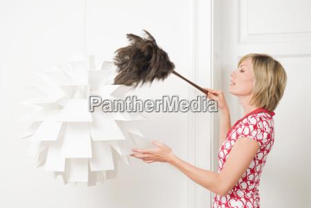 donna spolverare una lampada con un