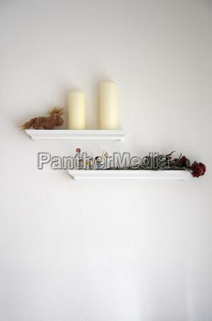 rosa essiccata e candele su mensola