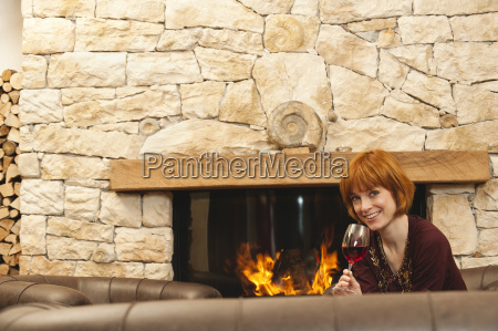 woman drinking wine by fireplace smiling