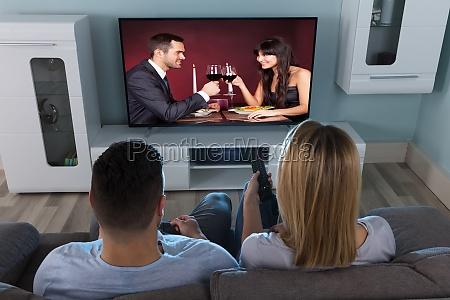 coppia guardare la televisione a casa
