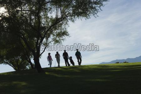 silhouette golfers walking on golf course