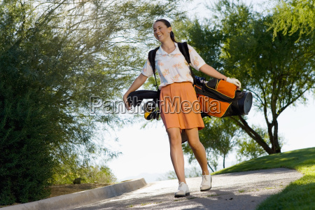 young woman carrying golf bag