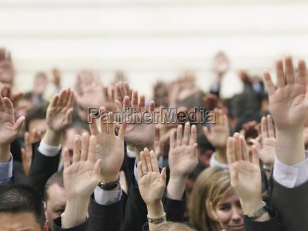 business crowd alza le mani