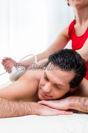 man having back massage in wellness