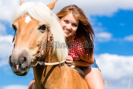 donna a cavallo nel prato estivo