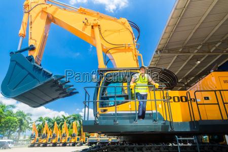 asian worker on shovel excavator construction