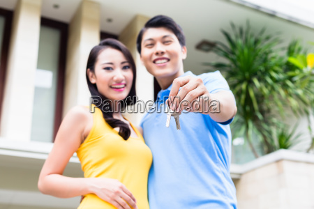 chinese couple showing keys to their