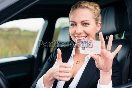 woman showing driving license and thumbs