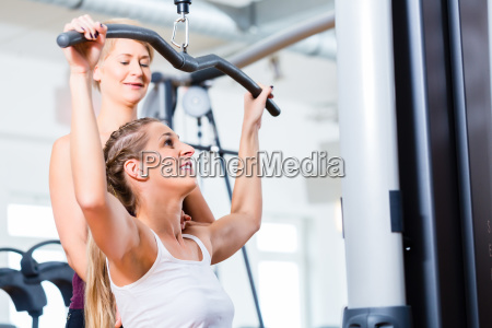 woman doing back training with trainer