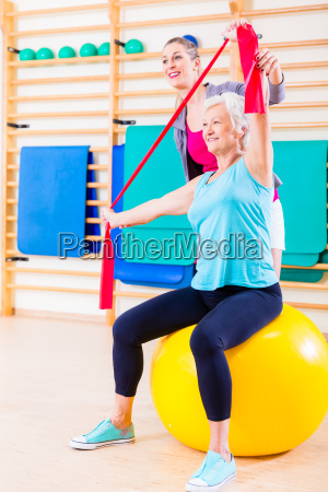 senior donna con elastico in fitness