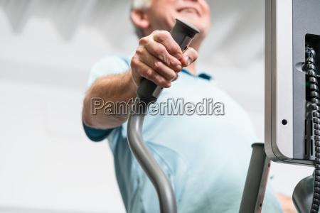 elderly man training on cross trainer