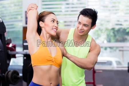 asian man helping girl stretching and