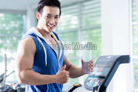 smiling young man on treadmill holding