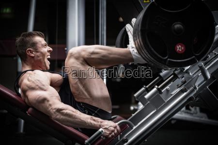 man in gym training at leg