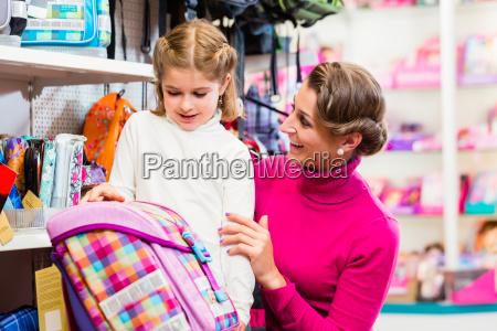 mother and kid buying school satchel