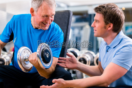 senior man and trainer at exercise