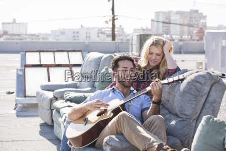 couple on rooptop sitting on sofa
