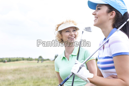 cheerful female friends at golf course