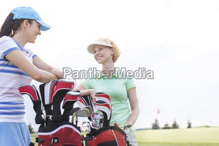 happy female golfers talking at golf