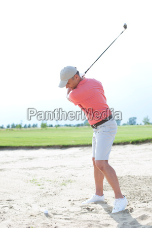 middle aged man swinging at golf