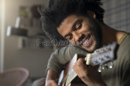 smiling man playing guitar