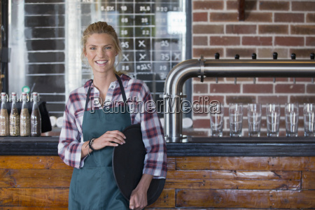 portrait of waitress standing by counter