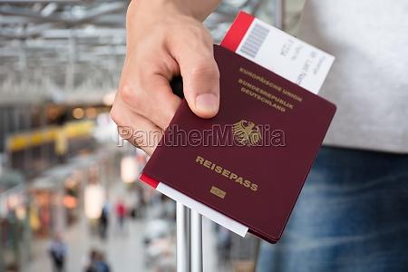 persona con passaporto bagagli e biglietti