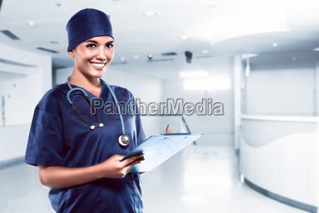 bella asiatico medico sorridente con ospedale