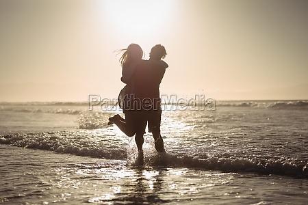 silhouette coppia godendo sulla riva in