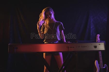 female musician playing piano in nightclub