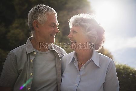 coppia anziana sorridente che si guarda
