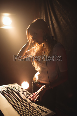 female dj playing music in illuminated