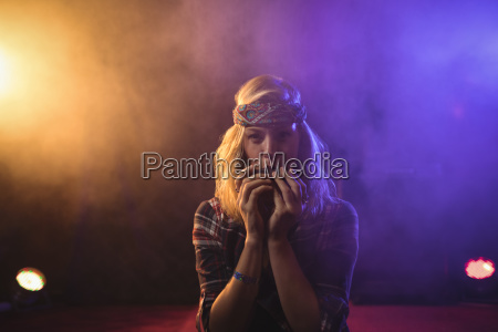 confident female musician playing harmonica in