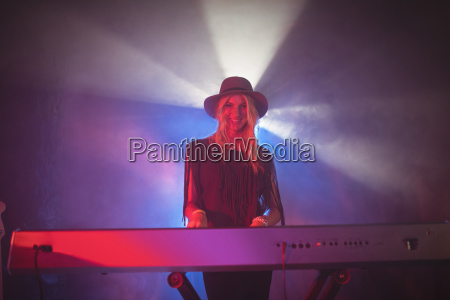smiling female playing piano on stage