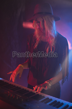 female performer playing piano in nightclub