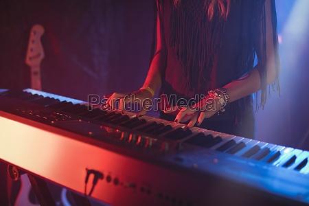 female playing piano in illuminated nightclub