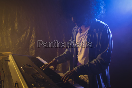 male musician playing piano in illuminated