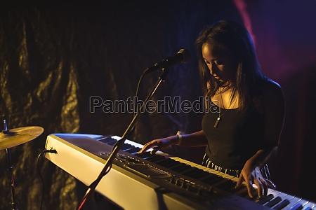 musician playing piano in illuminated nightclub