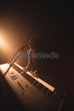 enthusiastic female singer playing piano at