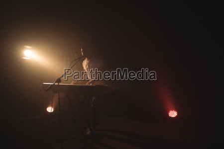 male singer playing piano in illuminated