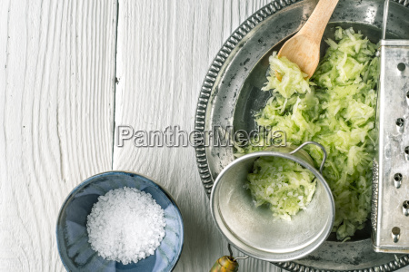 grated cucumber with strainer and salt