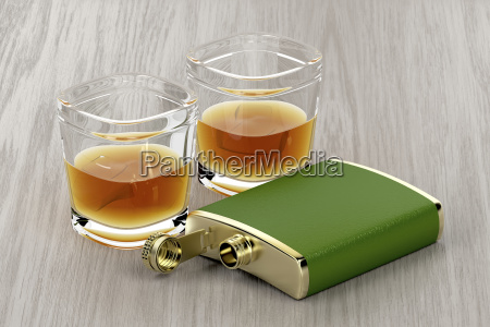 fiaschetta verde e bicchieri di whisky