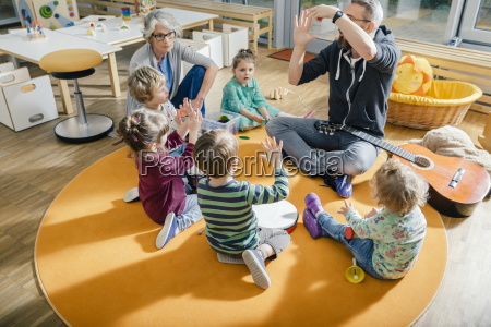 children and teachers playing and making