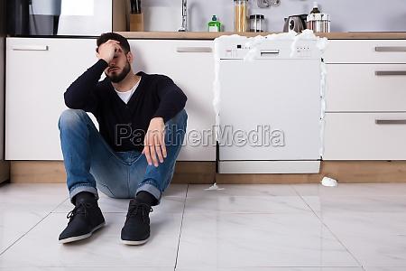 upset man sitting next to dishwasher