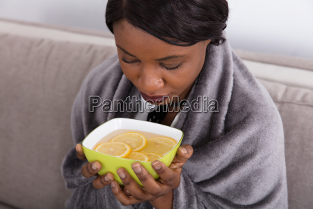 sick woman holding bowl with sliced